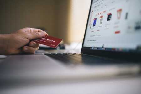 Male holding a card whilst online shopping