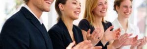 One male, three females smiling and clapping