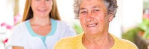 Photo of happy elderly woman with her young caregiver