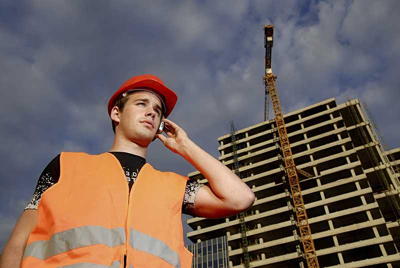 Worker on phone at building site
