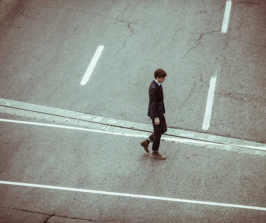 Male walking on his own over a road