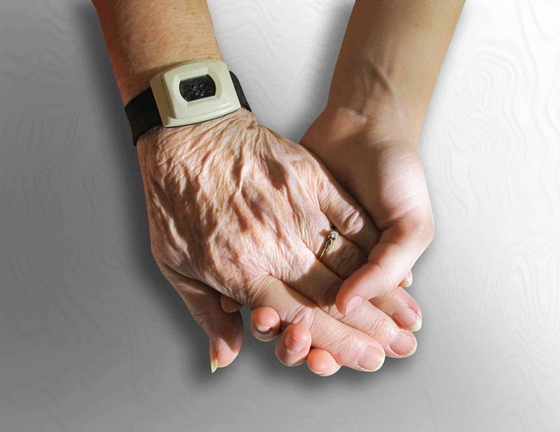 Elderly person holding a carers hand