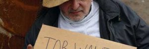 Homeless man holding job wanted sign