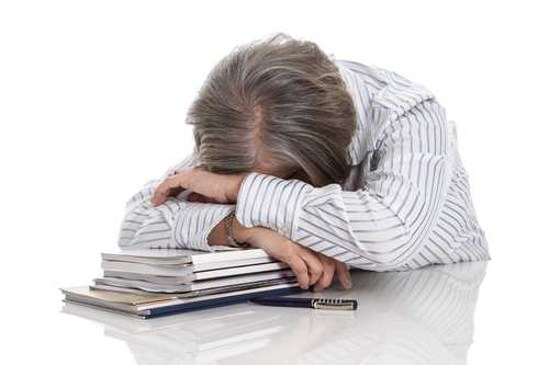 Grey haired woman sleeping on books - overworked isolated on white background - burn out