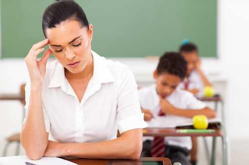stressed female primary school teacher having headache in classroom
