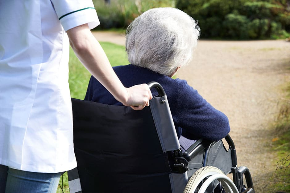 Lone home carer pushing elderly woman in wheelchair