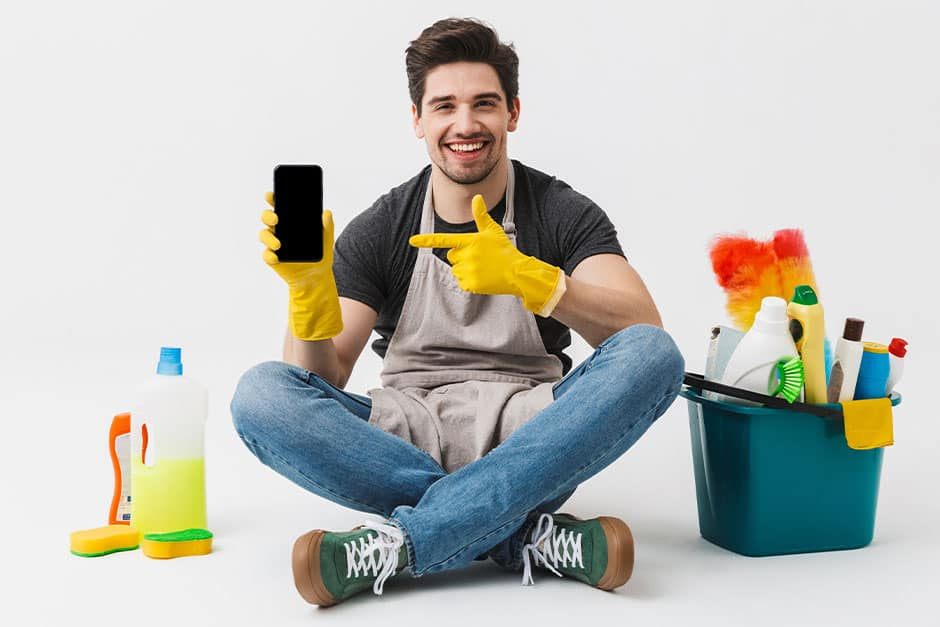 Happy cleaner holding a smartphone