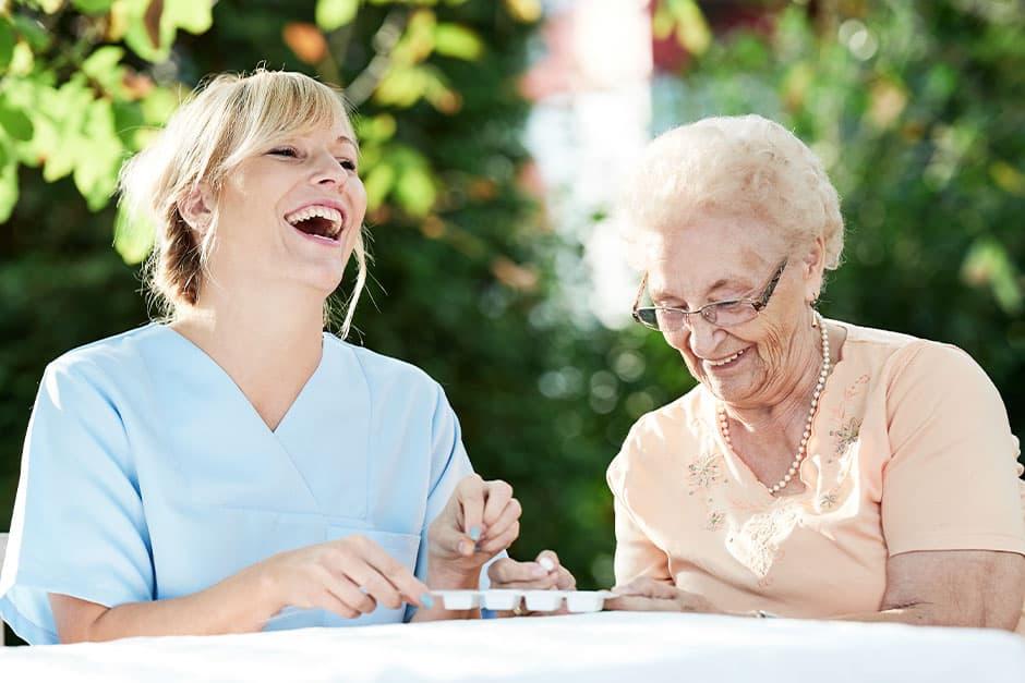 Carer with senior laughing, taking medication