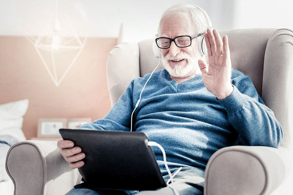 Senior citizen using tablet technology and headphones