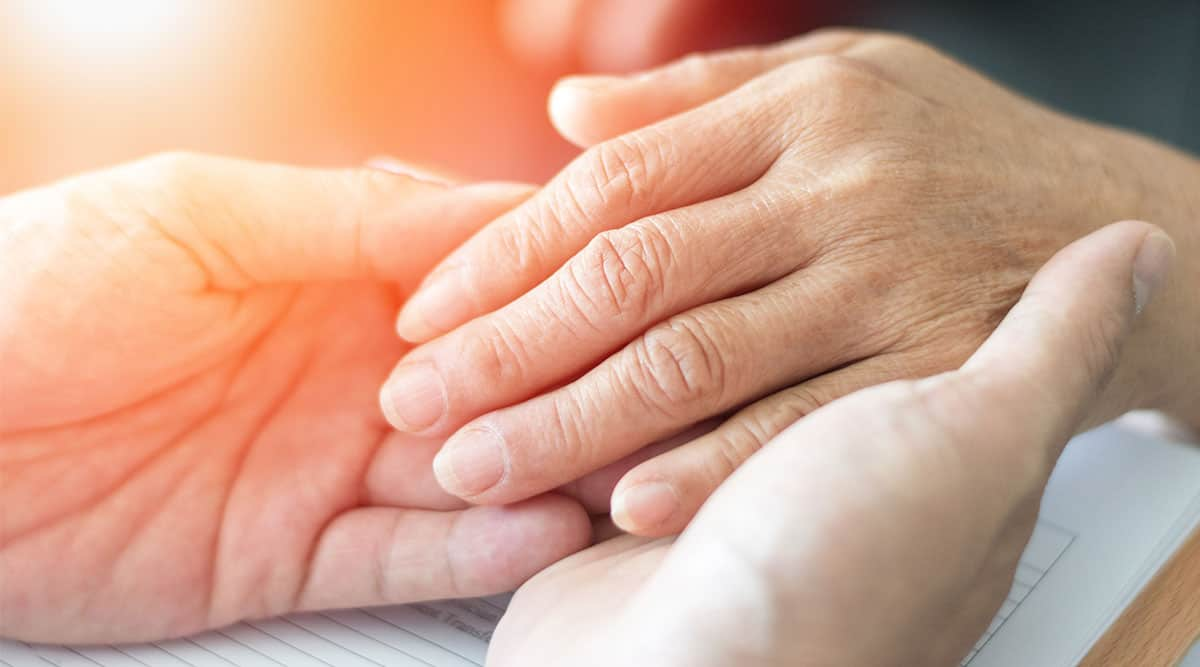 A domiciliary care worker holds an elderly person's hands