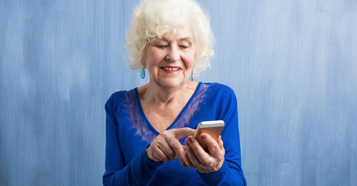 Senior lady in blue using a smartphone